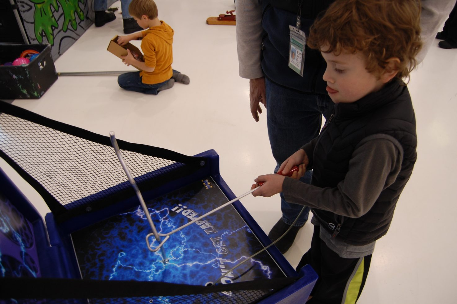 Boy playing shockwave carnival game