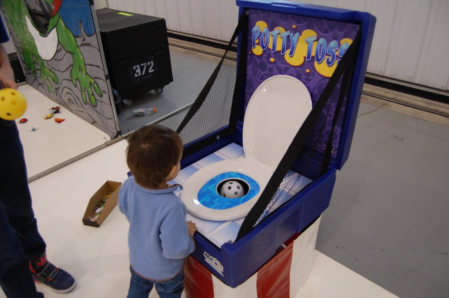 Boy playing potty toss carnival game