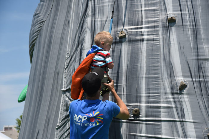 little boy climbing tiki island climbing wall with operator helping