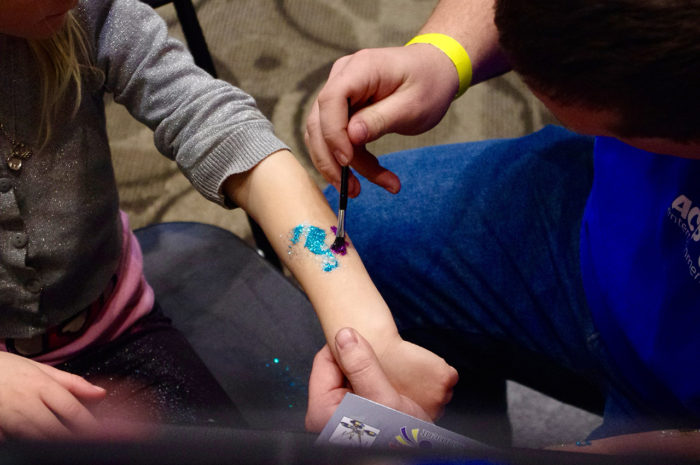 artist putting glitter tattoo on kids arm