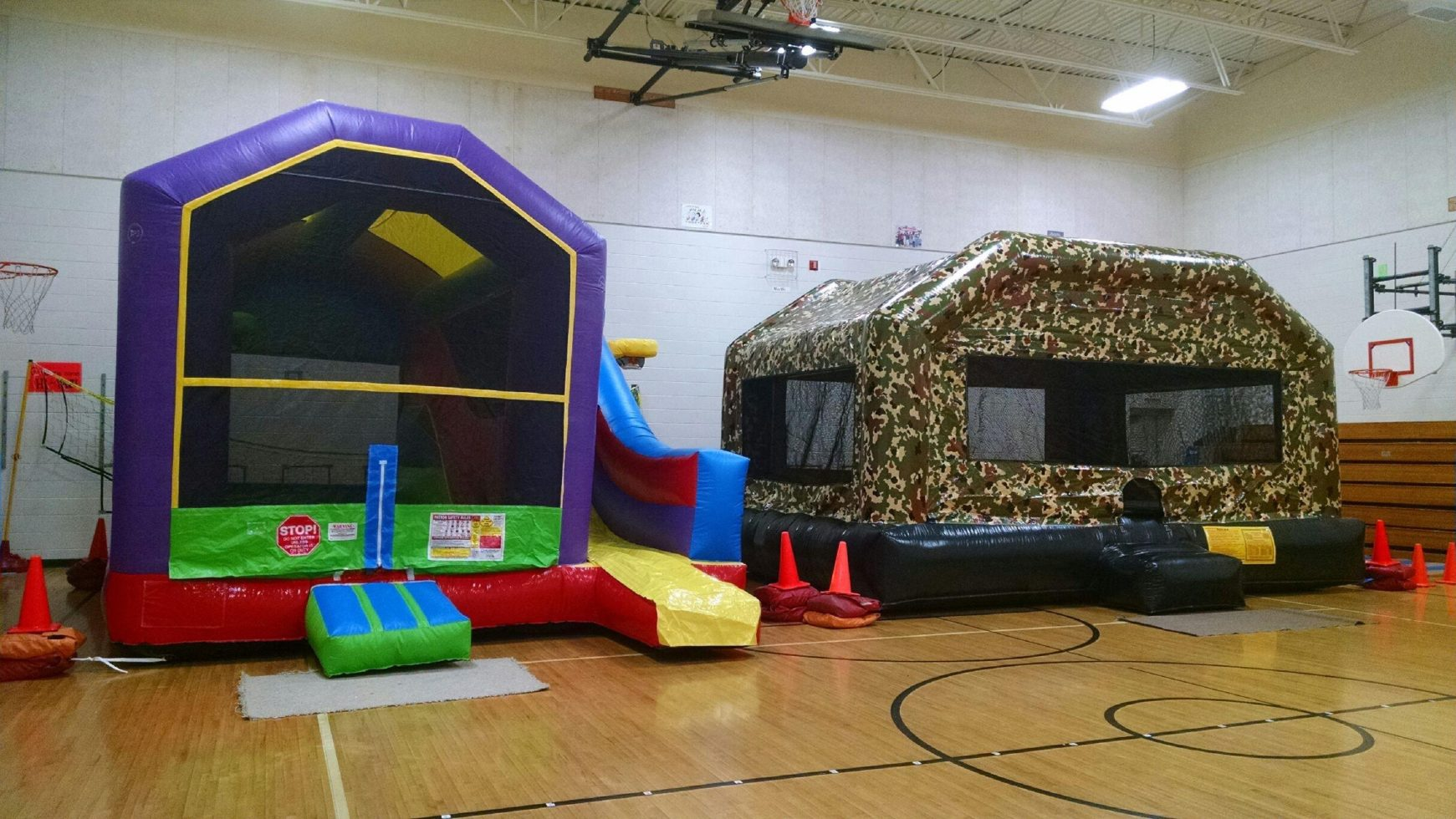 Camo bounce house setup inside gym