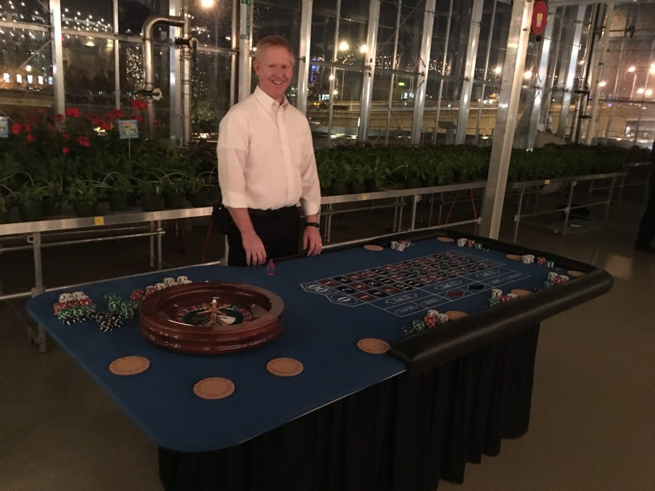 Casino dealer standing behind roulette table