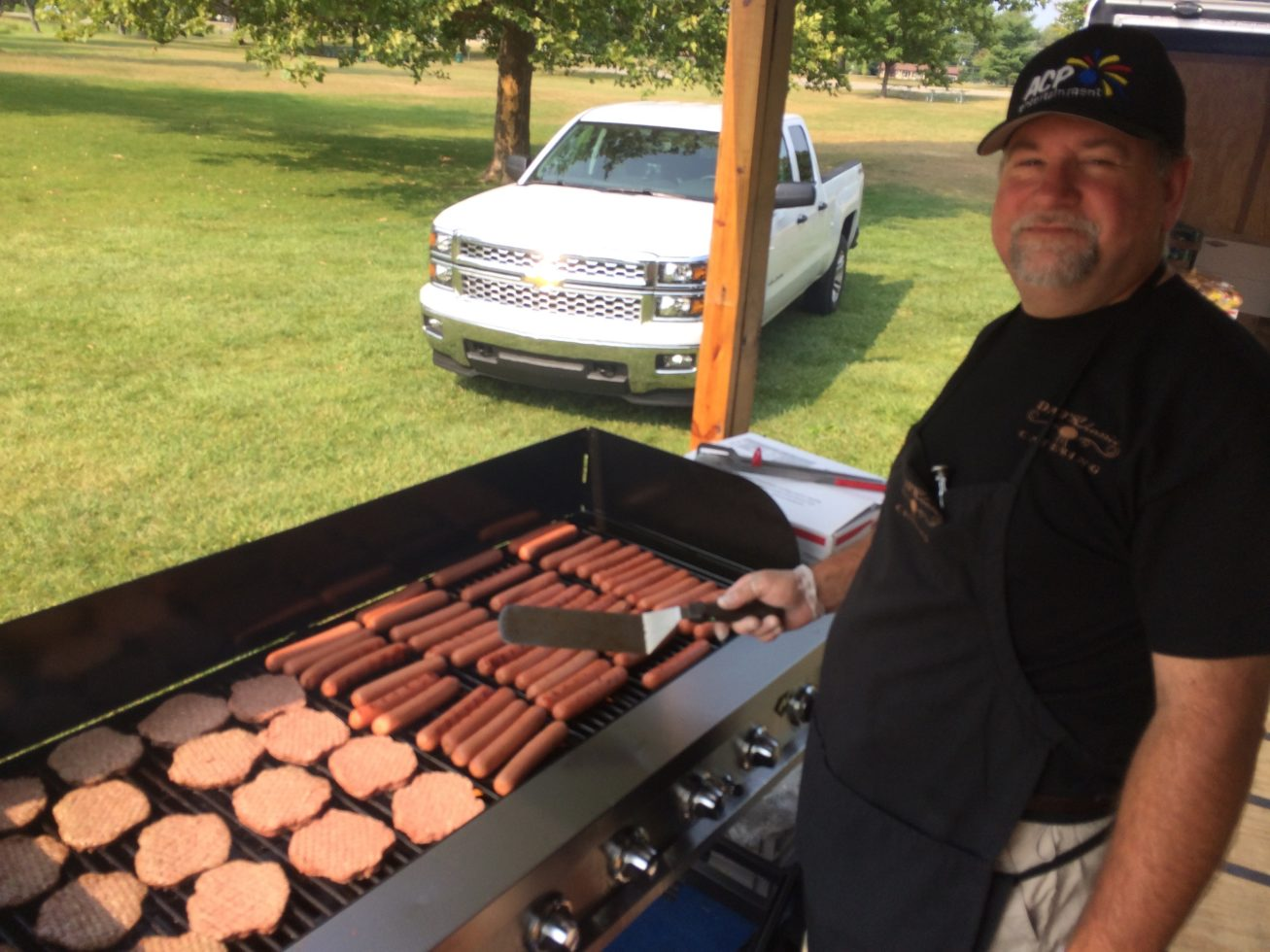 Cooking hamburgers and hot dogs on the grill