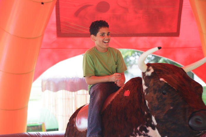 young boy riding mechanical bull