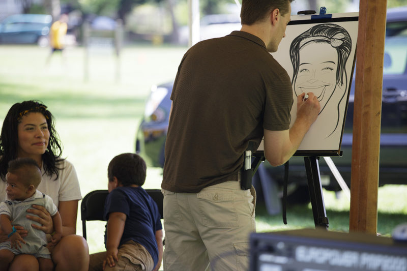 caricature artist draws smiling woman