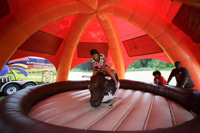young girl rides mechanical bull while people watch