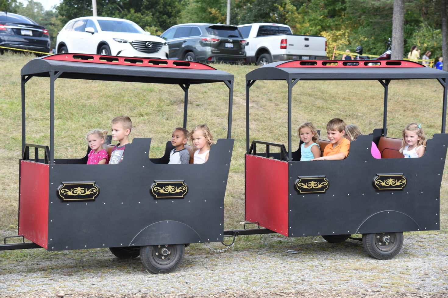 Kids on 2 different train cars of trackless train