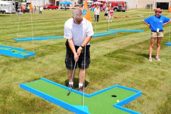 man playing mini golf