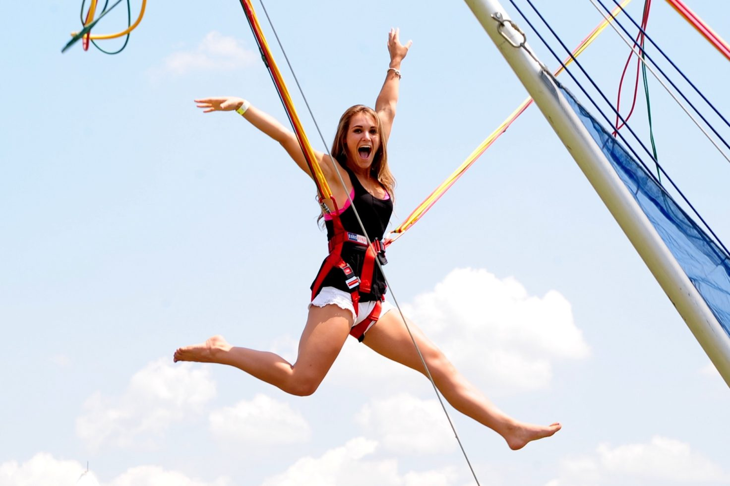 young woman doing air jumps on bungee trampoline