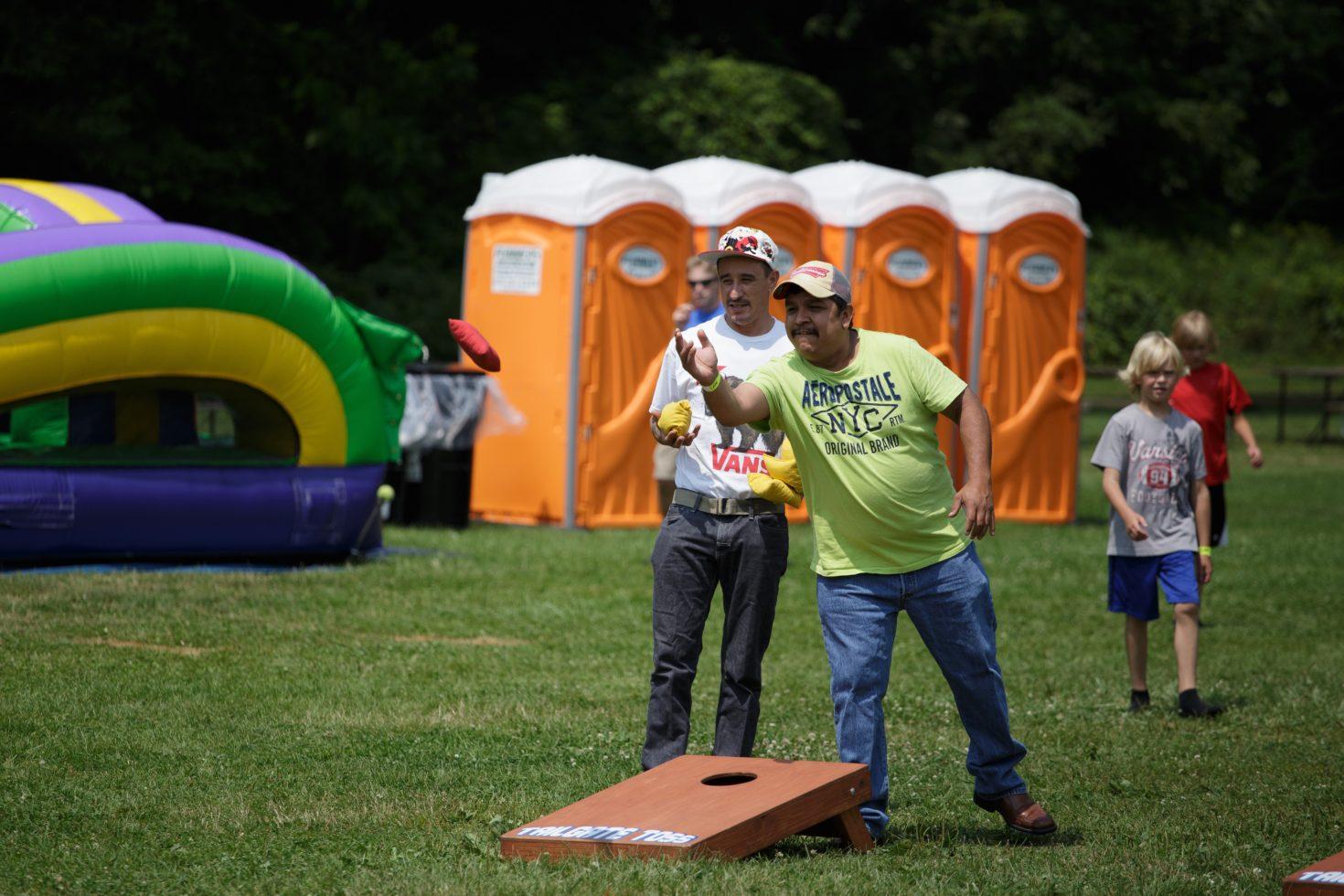 Men playing tailgate toss game
