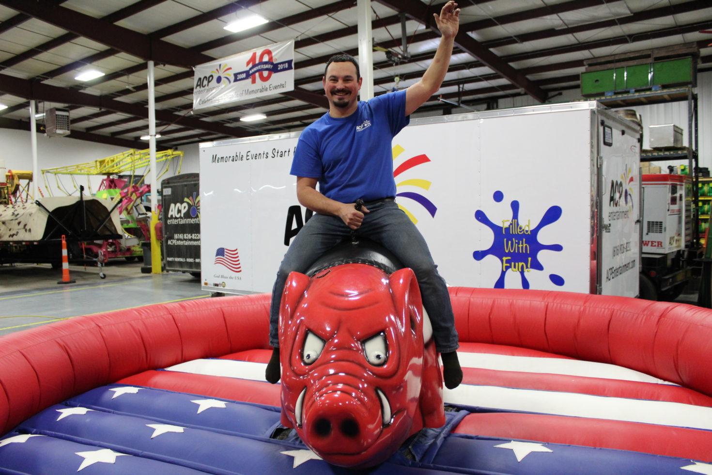 Guy riding mechanical hog pig ride michigan