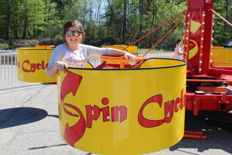Girl in spin cycle tubs of fun carnival ride rental